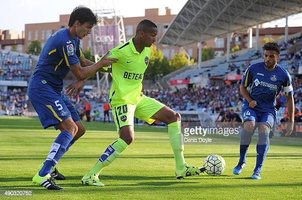 Deyverson of Levante is tackled by Santiago Vergini and Pedro Leon of Getafe during the La liga match between Getafe and Levante at estadio Coliseum...