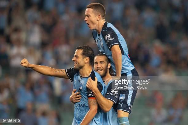 Deyvison Rogerio da Silva Bobo of the Sydney celebrates scoring his second goal with Joshua Brillante and Brandon O'Neill during the round 26 ALeague...