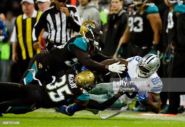 Dez Bryant of the Dallas Cowboys is brought down by Geno Hayes of the Jacksonville Jaguars and Demetrius McCray of the Jacksonville Jaguars during...