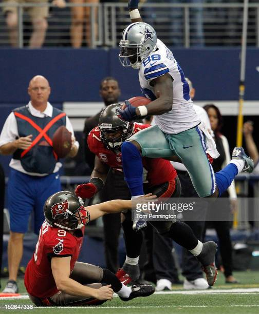 Dez Bryant of the Dallas Cowboys returns a punt against Adam Hayward and Michael Koenen of the Tampa Bay Buccaneers at Cowboys Stadium on September...