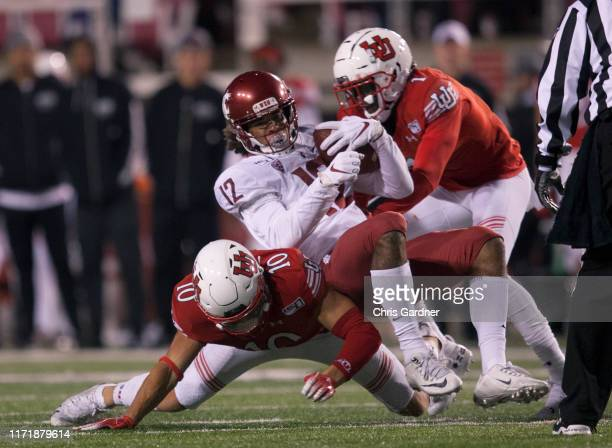Dezmon Patmon of the Washington State Cougars is tackled by Jaylon Johnson and R J Hubert at RiceEccles Stadium on September 28 2019 in Salt Lake...