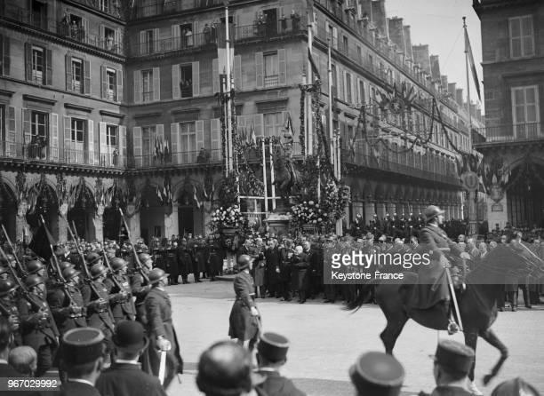 Défilé des troupes devant les membres du gouvernement au pied de la statue à Paris France le 19 mai 1935