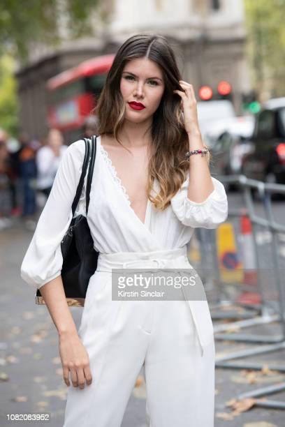 Dgital Influencer Alba Riquelme wears a BCBG jumpsuit and an Aldo bag during London Fashion Week September 2018 on September 18 2018 in London England