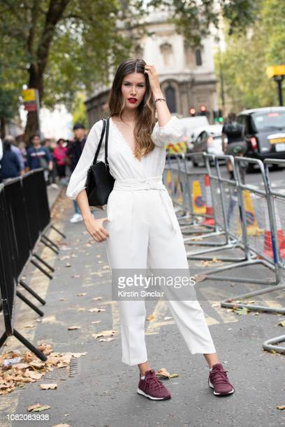 Dgital Influencer Alba Riquelme wears a BCBG jumpsuit and trainers Aldo bag during London Fashion Week September 2018 on September 18 2018 in London...