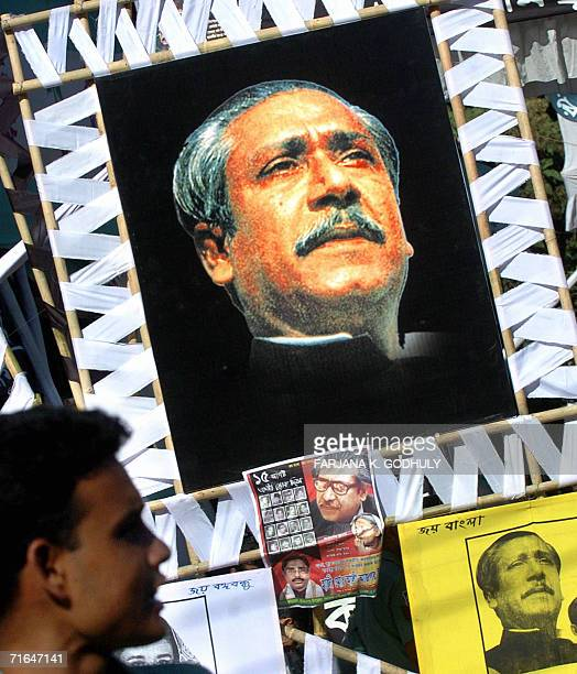 A Bangladeshi man looks at portraits of Bangabandhu Sheikh Mujibur Rahman during a six hour nation wide general strike called by the main opposition...