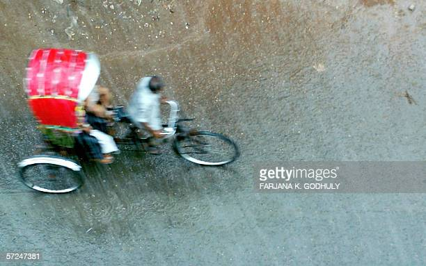 A Bangladeshi rickshaw puller carries passengers through a heavy downpour in Dhaka 04 April 2006 Seasonal thunderstorms accompanied by rain and hail...