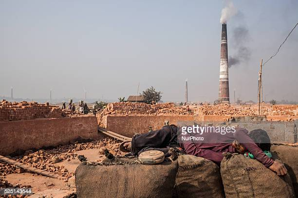 Dhaka, Bangladesh – A worker is taking a nap in the brickfield. The world is going through a speedy urbanization and Bangladesh is not an exception...