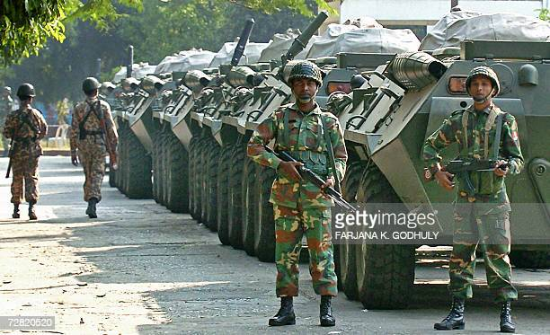 Bangladeshi army soldiers stand guard in front of armored vehicles near the President House at Gulistan in Dhaka 14 December 2006 Bangladesh's...