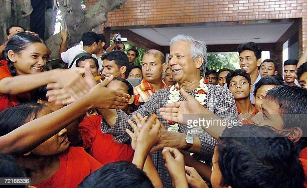 Bangladeshi Nobel Peace Prize winner Muhammad Yunus shakes hands with school children outside his office in Dhaka14 October 2006 one day after...