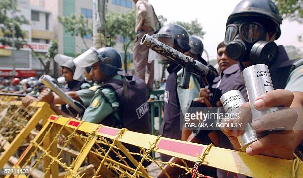 Bangladeshi riot policemen hold tear gas shells at the ready as they stand behind a barricade during a protest in Dhaka 30 March 2006 At least 29...