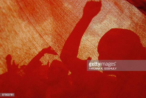 Bangladeshi workers shout slogans behind from a red flag during a demonstration to mark May Day in Dhaka 01 May 2006 Demanding better wages a weekly...