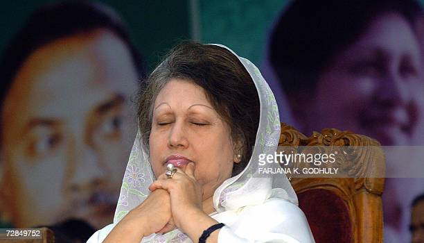 Former Bangladeshi Prime Minister and leader of the Bangladesh Nationalist Party Khaleda Zia gestures while sitting in front of a portrait of her and...