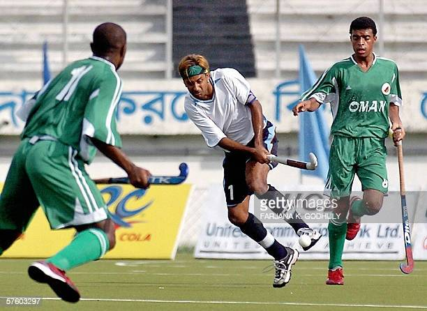 Hokg Kong hockey player Akbar Ali passes the ball under pressure from Oman opponents Musain Abdullah and Shahab Rabeea during Jamuna Bank Asian Games...