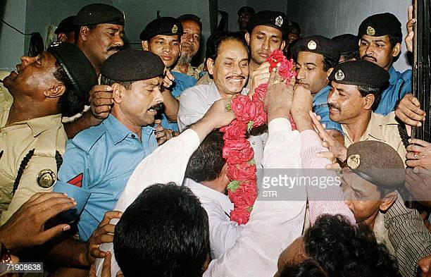 In this picture taken 09 April 2001 Bangladesh's deposed military dictator Hussain Muhammad Ershad issurrounded by police as he receives a garland of...