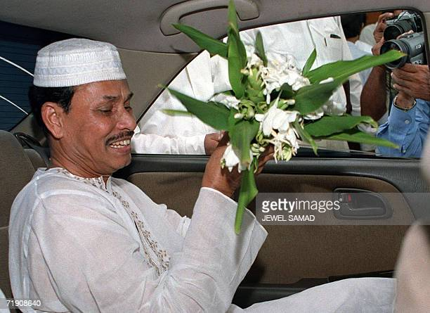 In this picture taken 25 August 2000 Bangladesh's deposed president Hussain Muhammad Ershad receives flowers from a supporter after Friday noon...