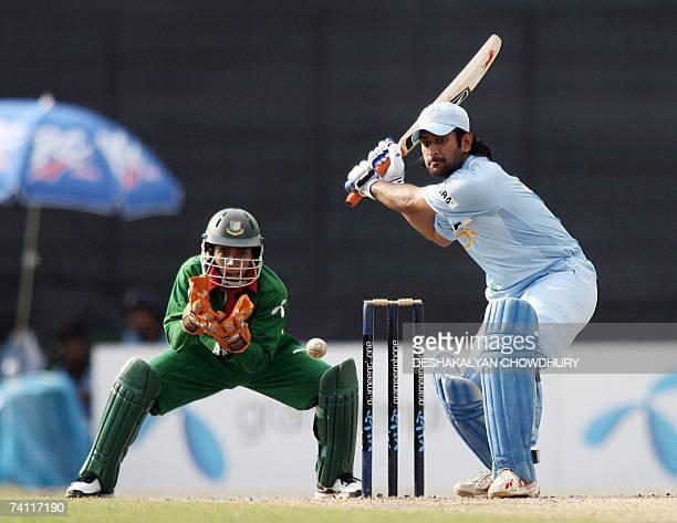 Indian batsman Mahendra Singh Dhoni plays a shot as Bangladeshi wicketkeeper Mushfiqur Rahim eyes the ball during the first One Day International...