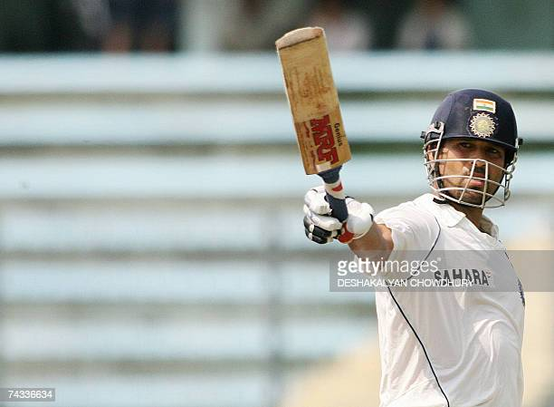 Indian cricketer Sachin Tendulkar raises his bat after scoring a century during the second day of the second Test match between India and Bangladesh...