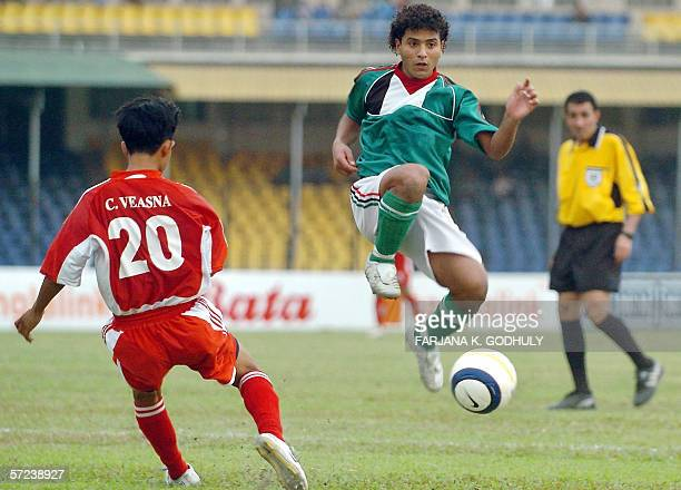 Palestinian footballer Al Sweirki Ibrahim leaps into the air as he vies for the ball with Cambodian opponent Chea Veasna during a match between...