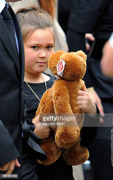 Dhakota Williams, daughter of slain gangland killer Carl Williams, carries a teddy bear as she leaves the church after his funeral service, in...
