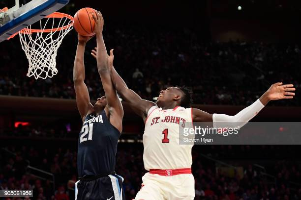 Dhamir CosbyRoundtree of the Villanova Wildcats dunks the ball past Bashir Ahmed of the St John's Red Storm during an NCAA men's basketball game at...