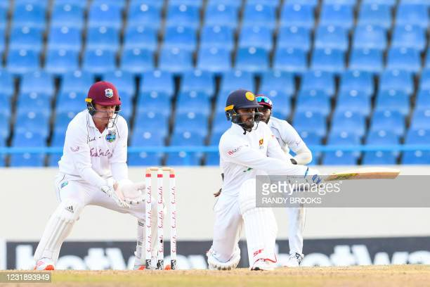 Dhananjaya de Silva of Sri Lanka hits 4 as Joshua de Silva of West Indies watch during day 3 of the 1st Test between West Indies and Sri Lanka at...