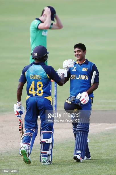 Dhananjaya Lakshan of Sri Lanka celebrates scoring a century with teammate Kamindu Mendis during the ICC U19 Cricket World Cup match between Sri...