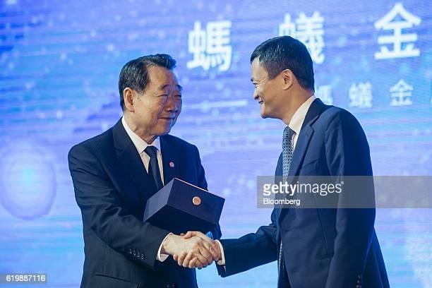 Dhanin Chearavanont billionaire and chairman of Charoen Pokphand Group Co left shakes hands with billionaire Jack Ma chairman of Alibaba Group...