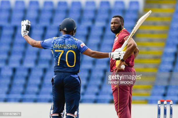Dhanushka Gunathilaka of Sri Lanka and Kieron Pollard of West Indies speak during the 1st ODI match between West Indies and Sri Lanka at Vivian...