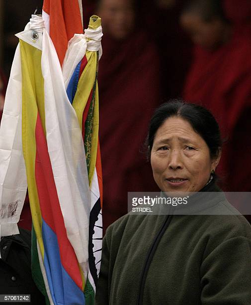 An exiled Tibetan woman holds Indian and Tibetan flags during a rally in Dharamshala12 March 2006 held to mark the Tibetan Women's Uprising of 1959...