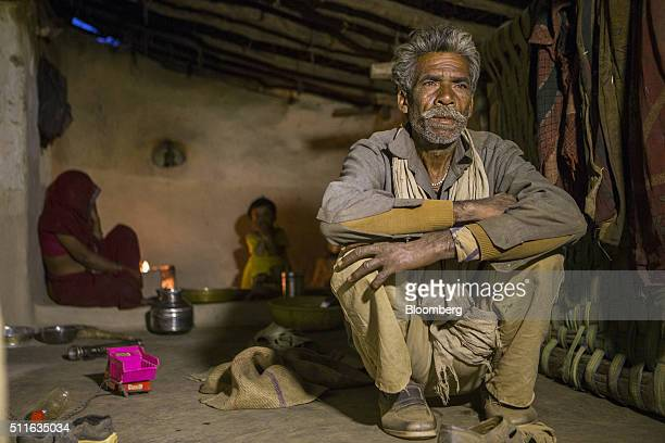 Dharmu Sahariya right sits with his family at his home in the village of Sakara in Lalitpur district Madhya Pradesh India on Saturday Feb 9 2016...