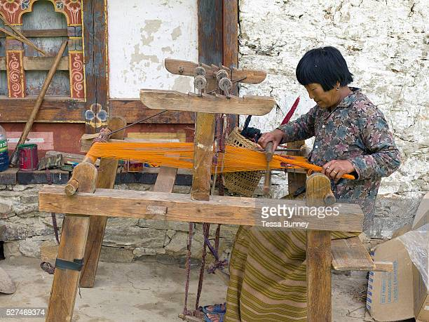 Dhenchen Chezom weaves a woollen yathra skarf on a Tibetan style loom outside her farmhouse in the Tang Valley Bumthang Central Bhutan Yathra is a...