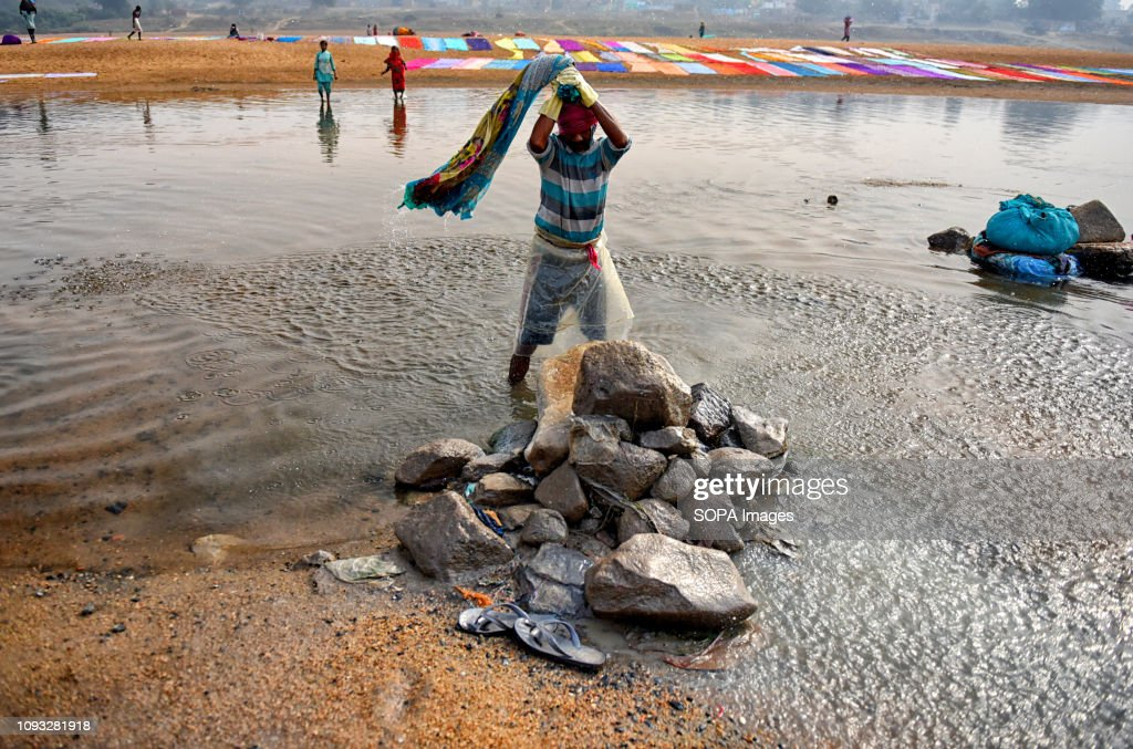 Dhobi seen washing the clothes on the river bank of Barakar... : Nachrichtenfoto