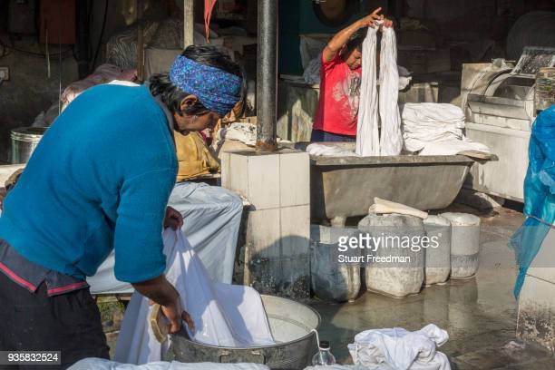 Dhobi wallahs or washermen launder clothes and linen at the Devi Prasad Sadan Dhobi Ghat in New Delhi India The ghat is home to around 64 washermen...