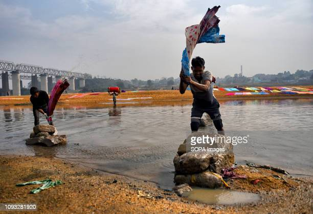 Dhobi's seen washing the clothes on the river bank of Barakar in the eastern part of India before spread them on the soil next to the river bank of...