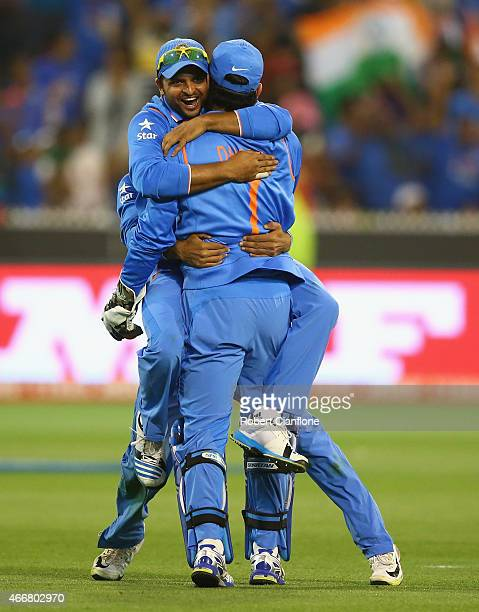 Dhoni and Suresh Raina of India celebrate taking the wicket of Soumya Sarkar of Bangladesh during the 2015 ICC Cricket World Cup match between India...