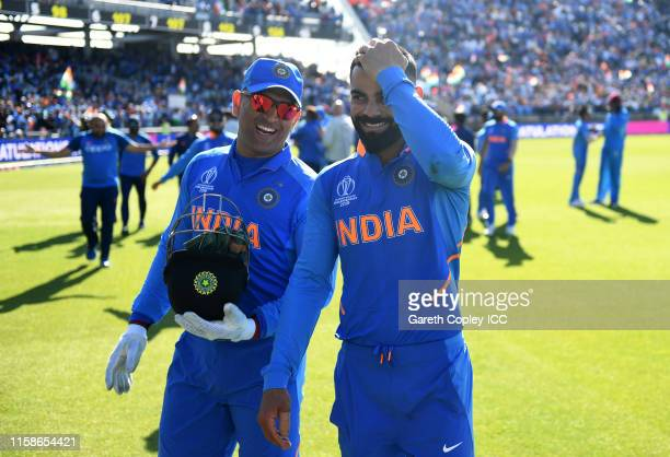 Dhoni and Virat Kohli of India chat during the Group Stage match of the ICC Cricket World Cup 2019 between West Indies and India at Old Trafford on...
