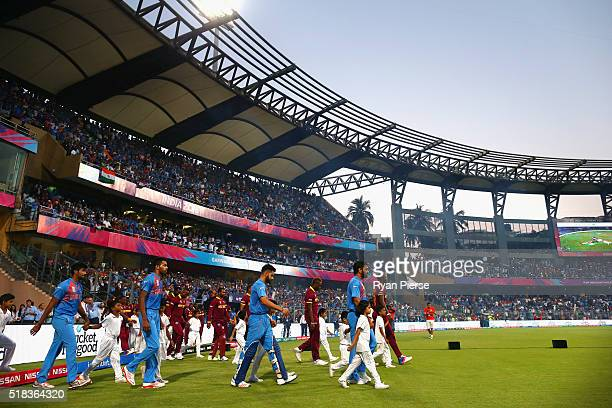 Dhoni Captain of India and Virat Kohli of India lead out their team during the ICC World Twenty20 India 2016 Semi Final match between West Indies and...