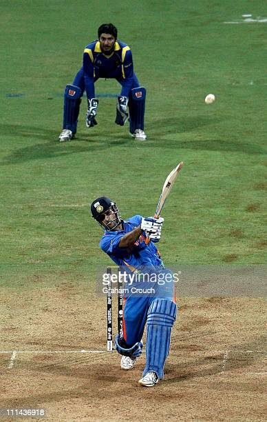 Dhoni captain of India hits the winning runs watched by Kumar Sangakkara captain of Sri Lanka to secure victory during the 2011 ICC World Cup Final...