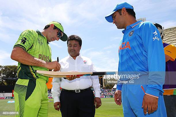 Dhoni of India and Shahid Afridi of Pakistan sign a bat for the Pepsi Mascot of the day during the 2015 ICC Cricket World Cup match between India and...