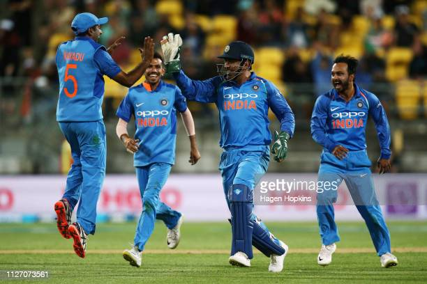 Dhoni of India celebrates with Ambati Rayudu after taking the wicket of Jimmy Neesham of New Zealandduring game five in the One Day International...