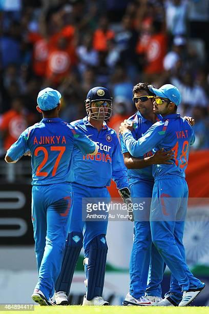 Dhoni of India celebrates with teammates Ravichandran Ashwin Virat Kohli and Ajinkya Rahane after dismissing Corey Anderson of New Zealand during the...
