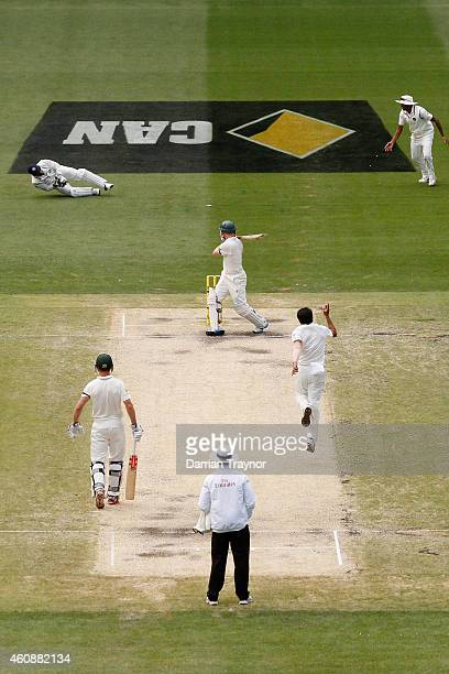 Dhoni of India dives for a catch off Chris Rogers of Australia during day four of the Third Test match between Australia and India at Melbourne...