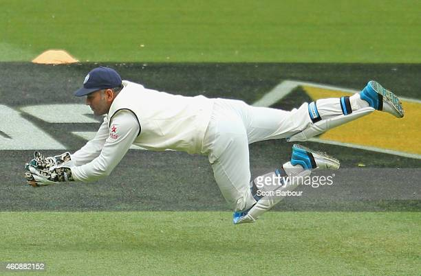 Dhoni of India dives to take a catch to dismiss Joe Burns of Australia during day four of the Third Test match between Australia and India at...