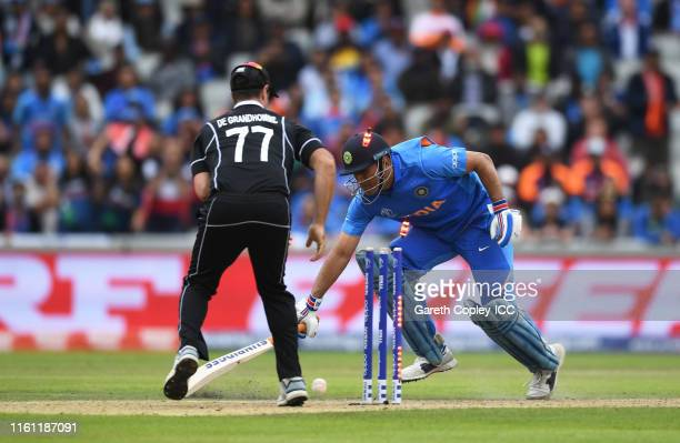 Dhoni of India is run out by Martin Guptill of New Zealand during the SemiFinal match of the ICC Cricket World Cup 2019 between India and New Zealand...