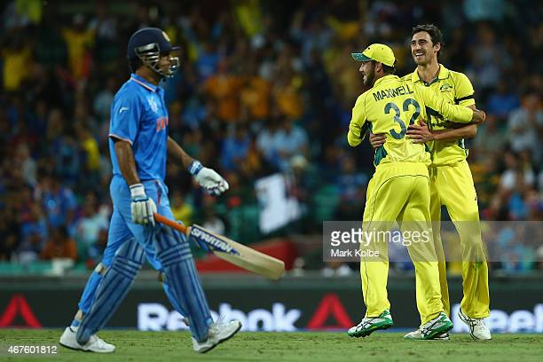 Dhoni of India looks dejected as Glenn Maxwell and Mitchell Starc of Australia celebrate his run out during the 2015 Cricket World Cup Semi Final...