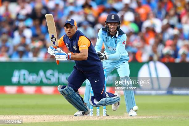 Dhoni of India plays to long on as England wicketkeeper Jos Buttler looks on during the Group Stage match of the ICC Cricket World Cup 2019 between...