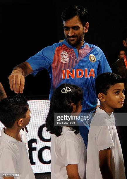M S Dhoni of India plays with a ceromonial child as they get ready for the national anthem during the ICC World Twenty20 India 2016 match between...