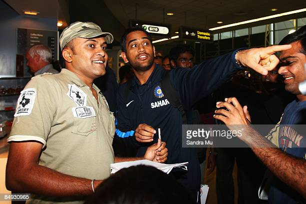 Dhoni of India points out Sachin Tendulkar to deter the fans at the arrivals hall as the Indian cricket team arrive at Auckland International Airport...