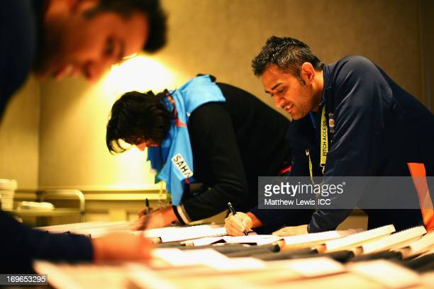 Dhoni of India signs cricket bats during an India Portrait Session at the Hyatt Hotel ahead of the ICC Champions Trophy at Edgbaston on May 30 2013...