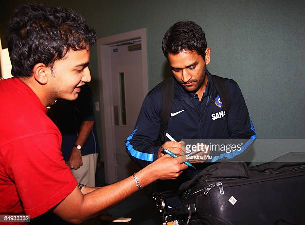Dhoni of India signs his autograph as he walks through the arrivals hall as the Indian cricket team arrive at Auckland International Airport on...